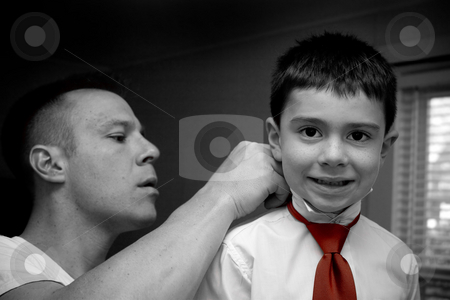 Father Helping Son Get Ready stock photo, A groom helps his son get ready by putting on his tie. by Todd Arena