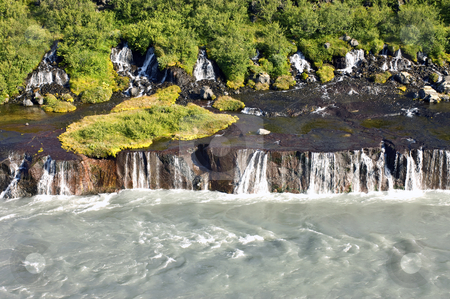 Hraunfossar stock photo, The spectacular Hraunfossar cascades, a waterfall in Iceland, where natural springs supply the water from the rhyolite mountains, covered with shrubs, bushes, grass and moss. by Corepics VOF
