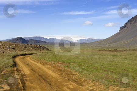 Iceland Inland Trail stock photo, A jeep track or dirt road in Iceland leading around the Hlodufell Volcano winding around remnants of volcanic eruptions, with a clear view of the Langjokull glacier in the distance by Corepics VOF