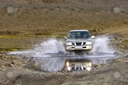 Crossing a river stock photo, A big four by four off road car crossing a river stream in the Icelandic Tundra by Corepics VOF