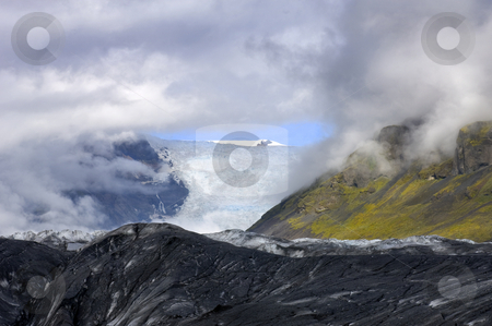 Glimpse at the Glacier stock photo, A glimpse through the clouds on the Svinafellsjokull glacier, one of the arms of the famous Icelandic Ice cap, the Vatnajokull by Corepics VOF