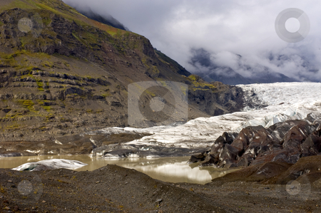 Glacier's End stock photo, The end of the Svinafellsjokul, Iceland, with a muddy pool with icebergs and moraines, lit by a glimmer of sunlight on an overcast day by Corepics VOF