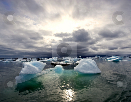 Turbulent sunset over Jokulsarlon Glacier Lake stock photo, Sunset over the famous Jokulsarlon glacier lake in Iceland, where the icebergs, originating from the Vatnajokull float. This location was used for various action movies. by Corepics VOF