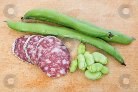 Salami slices and fava bean stock photo, Three salami slices with fava beans on a wood chopping board by ANTONIO SCARPI