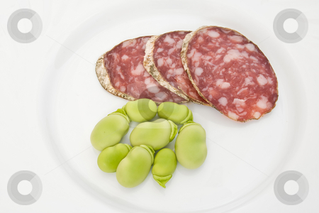 Fave e salame stock photo, Three salami slices with fava beans on a white dish by ANTONIO SCARPI