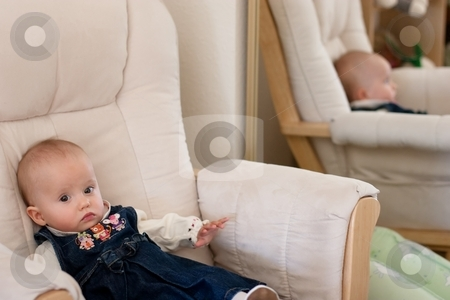 Sitting on a chair stock photo, Little caucasian baby girl in blue dress sitting on a chair by Mariusz Jurgielewicz