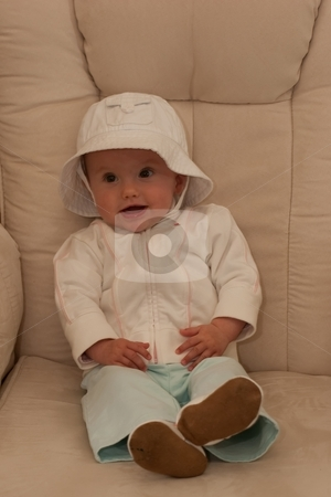 White hat stock photo, Cute little caucasian baby girl wearing white hat and sitting on a chair. by Mariusz Jurgielewicz