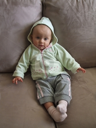 On the sofa stock photo, Little caucasian baby girl sitting on a sofa. by Mariusz Jurgielewicz