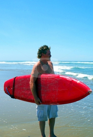 Surfer on the Beach stock photo, Man standing with his surfboard on the beach by Carol Grimes