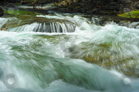 Rushing River Rapids stock photo, Clean clear water racing down the river bed over rocks and boulders creating rapids and small waterfall by Lynn Bendickson
