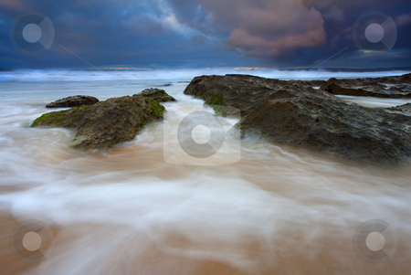 Storm Shadow stock photo, Storm clouds over Encounter Bay at Sunrise as the tides crash over and against the rocks scattered around the beach. by Mike Dawson