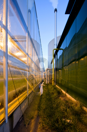 Glasshouse stock photo, The exterior glass fascade of a huge glasshouse with heating system and generator by Corepics VOF