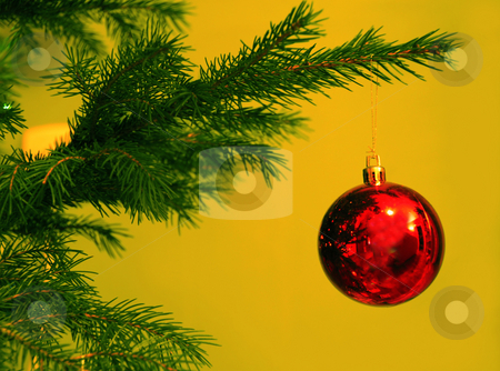 Christmas ball stock photo, Christmas red ball on green new year tree over yellow by Julija Sapic