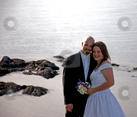 Attractive Bride & Groom Near Ocean stock photo, This attractive bridge and groom are embracing with the ocean in the background for a beautiful photo. by Valerie Garner