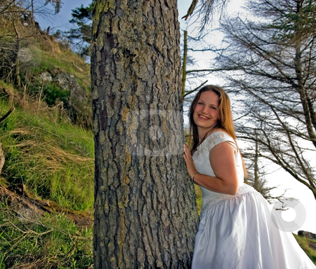 Pretty Bridge Leaning on Tree stock photo, This pretty Caucasian young bride is smiling and leaning against a tree on her wedding day. by Valerie Garner