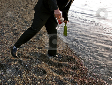 Man Off Balance Holding Wine stock photo, This man is falling off balance while holding two wine glasses and bottle at the beach. by Valerie Garner