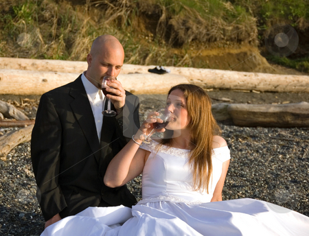 Bridge & Groom Sipping Wine on Beach stock photo, This young bride and groom are sipping red wine in their wedding clothing on a beach. by Valerie Garner