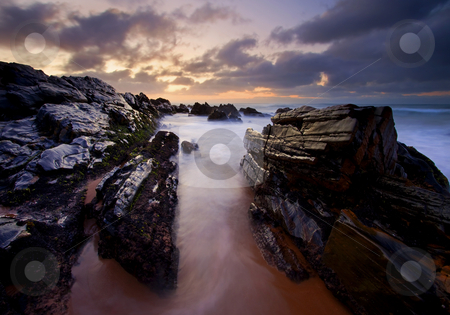 Stone Channel stock photo, Pre-dawn light as the incoming tides curl among the jagged rocks on Basham Beach by Mike Dawson