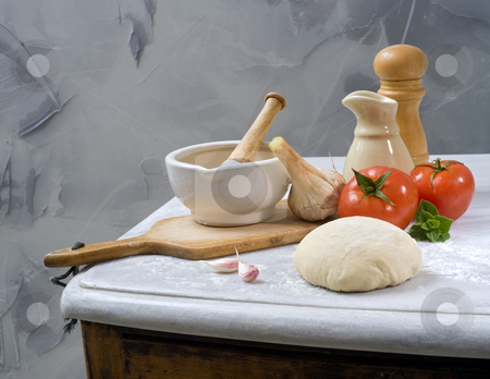 Baking ingredients stock photo, Dough, mortar and pestle, olive oil, tomatoes, oregano and garlic by Noam Armonn