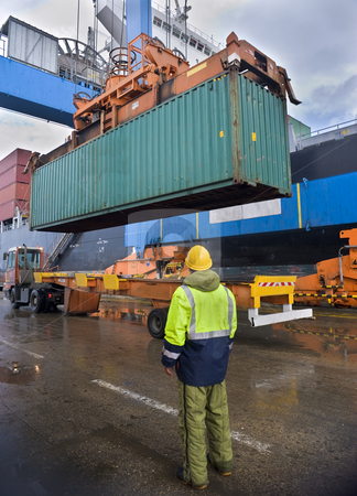 Container uploading stock photo, Worker supervising container uploading at dock by Noam Armonn