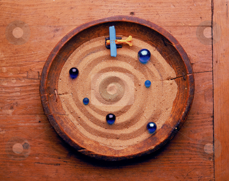 Cosmos stock photo, Toy airplane and marbles on a spiral shaped sand in a grugey wooden bowl on a wooden surface. by Noam Armonn