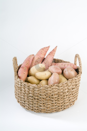 Three kind of potatoes stock photo, A basket full with yellow, red and sweet potatos. Isolated on white. by Noam Armonn