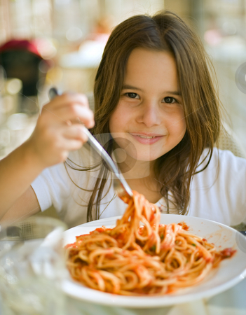 Child having spaghetti stock photo, Young girl eating spaghetti in restaurent by Noam Armonn