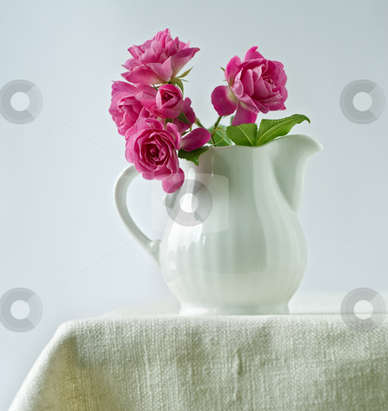 Bouquet of small roses stock photo, Bouquet of small roses in a ceramic milk pitcher by Noam Armonn