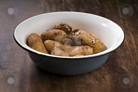 Fresh Potatoes from the garden stock photo, Dirty potatoes in an old bowl on a wooden table by Noam Armonn