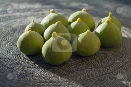 Green Figs on Beaten out metal Arabic Table stock photo, Green organic figs on an arabien beaten out metal table by Noam Armonn