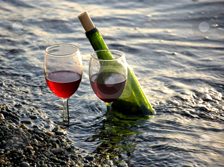 Wine Glasses and Bottle In Ocean stock photo, This still life is 2 wine glasses with red wine, and a bottle are in the sand with waves of the ocean coming in. by Valerie Garner