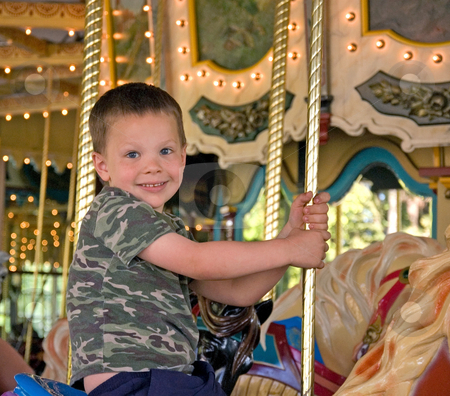 Little Boy Riding Carousel Horse stock photo, A very happy little 5 year old boy is riding a carousel horse on a merry go round for the first time. by Valerie Garner