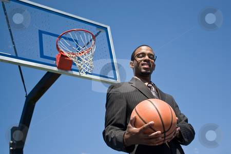 Basketball Pro stock photo, African American man in a business suit posing with a basketball.  He could be a coach player recruiter or trainer. by Todd Arena