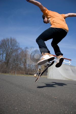 Skateboarder Jumping stock photo, Portrait of a young skateboarder performing a trick at the skate park. by Todd Arena
