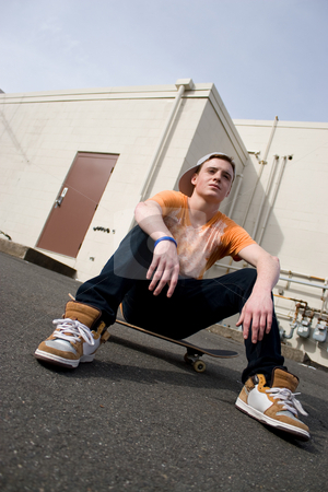 Skateboarder Hanging Out stock photo, A young skater resting on his skateboard. by Todd Arena