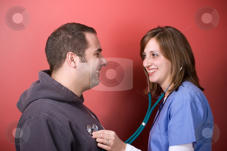 Checking His Heartbeat stock photo, A young doctor or nurse listening to the heartbeat of her patient with her stethoscope during an office visit. by Todd Arena