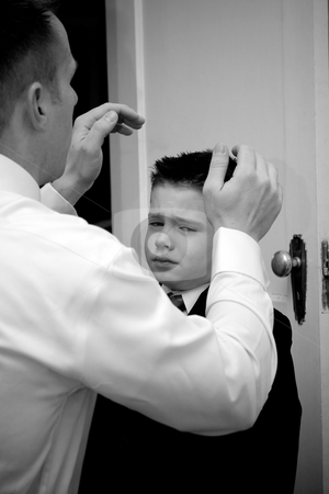 Father Helping Son Get Ready stock photo, A groom helps his son get ready by doing his hair. by Todd Arena