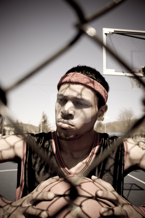 Basketball Player stock photo, A young basketball player gripping the ball tightly as viewed through the chain linked fence. by Todd Arena