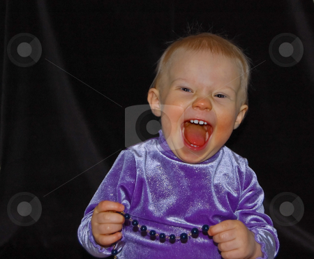 Toddler Excited Holding Necklace stock photo, Toddler is very excited and happy in this portrait photo with a black background.  She's a 1 year old Caucasian, wearing a shiny purple shirt and a very contagious smile. by Valerie Garner