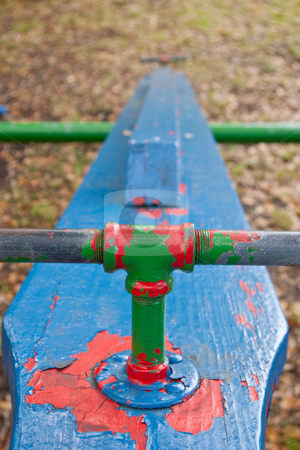 Chipping paint on old teeter-totter stock photo, Several layers of paint chipping off an old teeter-totter in a disused playground. by Steve Carroll
