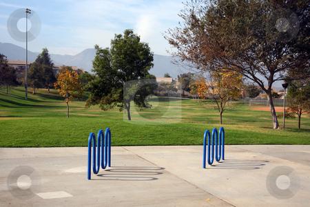 Bike rack park stock photo, Blue bike racks set in concrete in a lovely park by Stacy Barnett