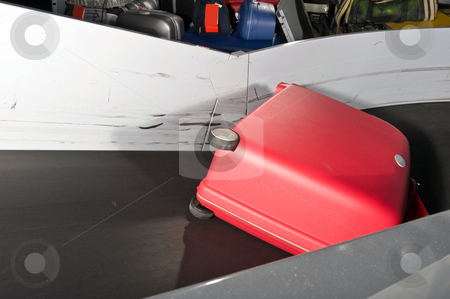 Luggage handling stock photo, A red suitcase on an airport conveyor belt being transported to an airplane by Corepics VOF