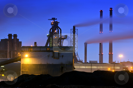 Blast Furnace stock photo, The menacing outline of a blast furnace, surrounded by chimneys and the industrial appliances of a steel plant at night by Corepics VOF