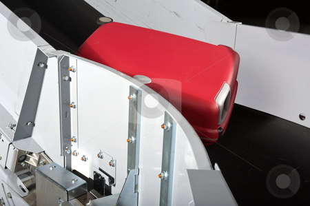 Luggage conveyor belt stock photo, A red suitcase on an airport conveyor belt being transported to an airplane by Corepics VOF