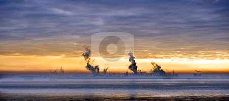Chemical skyline stock photo, Sunset over a chemical plant, situated along the water's edge by Corepics VOF