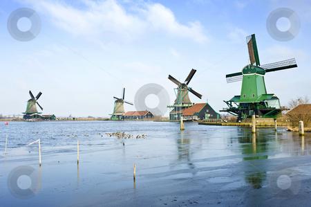Four windmills stock photo, Four typically Dutch windmills in De Zaanse Schans near de river Zaan in the Netherlands by Corepics VOF