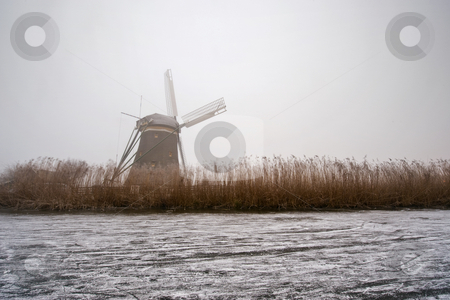 Dutch Winter Weather stock photo, The archetypal Dutch winter on a foggy morning on a frozen canal surrounded by reed, and a windmill by Corepics VOF