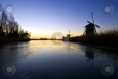 Windmills at sunrise stock photo, Three windmills at an early morning winter sunrise, reflecting in the cracked ice of a canal by Corepics VOF