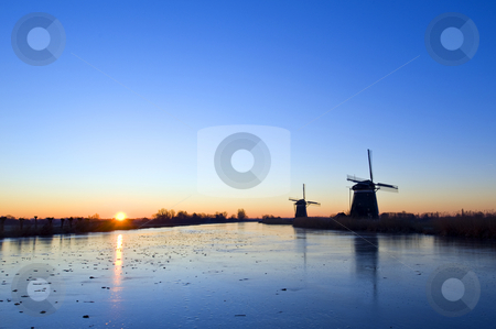 Winter Sunrise stock photo, The sun rises over rural holland in wintertime, with windmills and an ice covered, frozen, canal by Corepics VOF