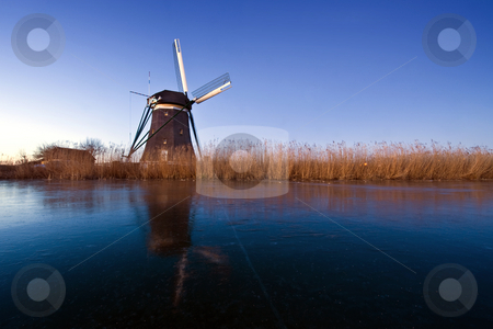 Dutch Winter scene stock photo, The first rays of sunlight hitting the reed waterfront and the windmill, perched on the side of an ice covered canal on a cold early winter morning by Corepics VOF